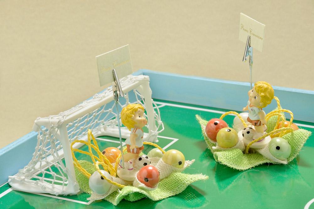 """Divertente azione di gioco tra calciatori in resina colorata, che palleggiano su un """"campetto regolamentare"""". Cinque palloni colorati ricoperti di cioccolato con nocciolina all'interno li circondano, aspettando il loro turno."""