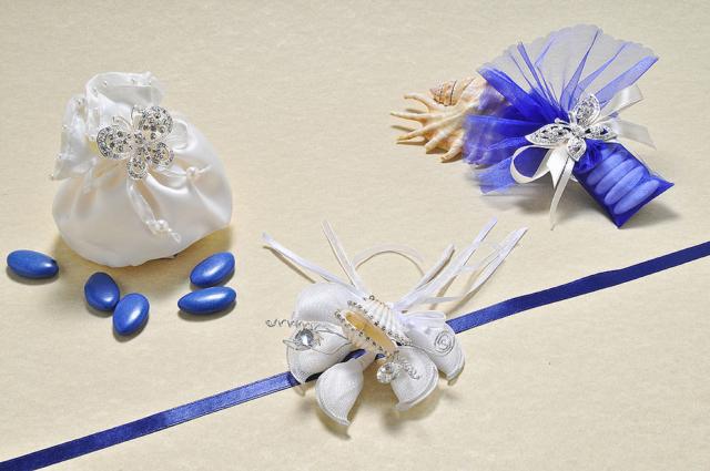 Sacchetto bombato in raso avorio con perle e tubino velato blu, impreziositi da ciondolo con farfalla argentata con strass. Un tocco luminoso il bouquet con la conchiglia vera contornata da strass.