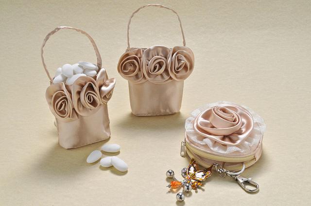 Stile elegante, raso e color champagne, danno forma alla pochette tonda e alla borsetta con manico. Un tocco di freschezza la scelta della rosa come decoro.