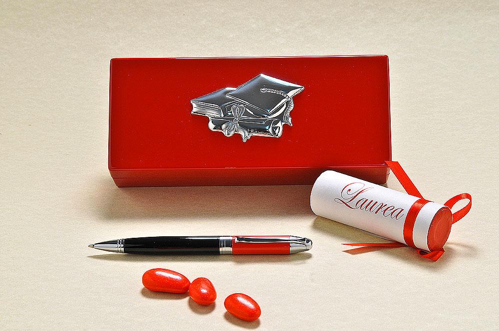 Elegante penna con bauletto in legno laccato rosso e placca in argento 925, simbolo del traguardo raggiunto. Come segnaposto, viene proposta una versione rivisitata di scatolina portaconfetti, a forma cilindrica.