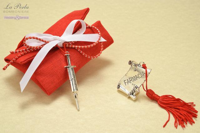 Pergamena in zama personalizzata con le diverse Facoltà. Ecco Farmacia e accanto, la siringa che simboleggia Infermieristica su una bustina di cotone rosso made in Italy.