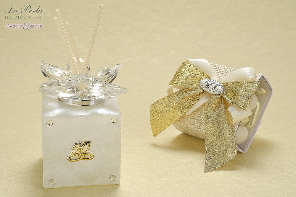 Raffinato, elegante e moderno il Profumatore per ambiente in vetro marmorizzato e placca in argento con 50° e fedi oro. E come segnaposto la Scatolina portaconfetti in pvc con placca 50°.