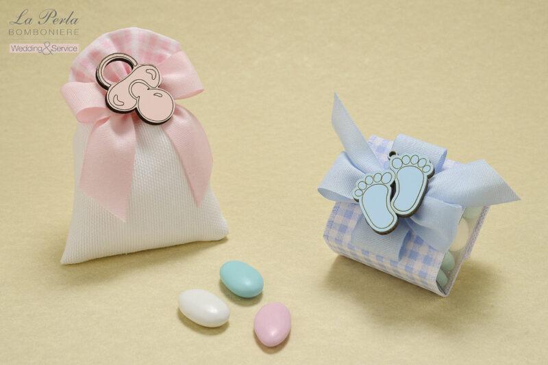 Ciucciotto rosa e impronte di piedini azzurri sono le calamite in legno che abbelliscono il sacchettino in cotone e la scatolina in pvc con decori a quadretti bianco-rosa e bianco-azzurri.