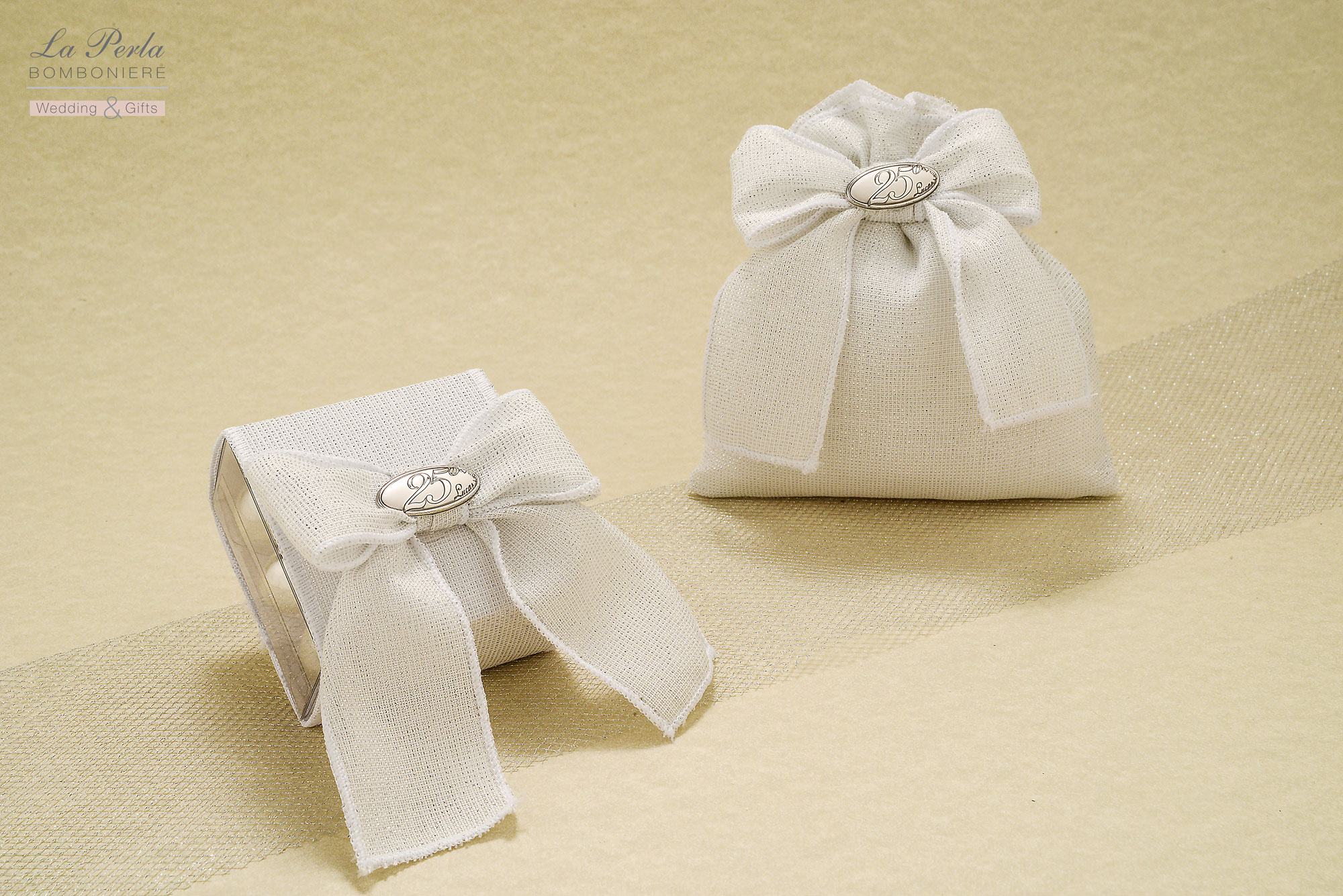Scatolina in pvc e sacchettino in tessuto laminato argento con targhetta 25° in argento. Molto delicato e raffinato la presenza dell'argento sul tessuto.