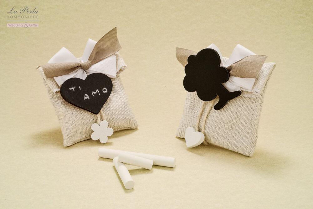 Perfetta per scrivere un breve messaggio d'amore, la Lavagnetta con mollettina applicata su bustina rettangolare in tessuto di cotone color sabbia. Creazione tutta italiana.