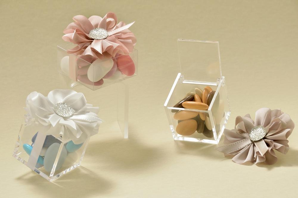 Cubo portaconfetti in plexiglass cm. 5 x 5 x 5 e scatolina in PVC alimentare cm. 6 x 6 x 3, abbelliti da una margherita dai petali di raso, con pistillo glitterato. I confetti sfumati lilla, turchese e marrone, ripropongono rispettivamente, il tema della primavera, del mare e dell'autunno.