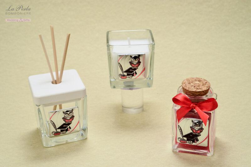 Gufetto e cappello, simboli della Laurea, in questa targhetta in argento bilaminato, applicati su profumatore, candela e bottiglietta in vetro.