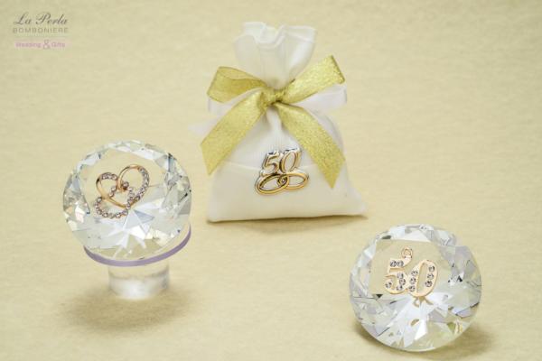 Debora Carlucci firma il prisma in cristallo con due cuori intrecciati dorati e il 50 simbolo delle Nozze d'Oro. Sacchettino in cotone con targhetta 50° in argento bilaminato, come segnaposto.