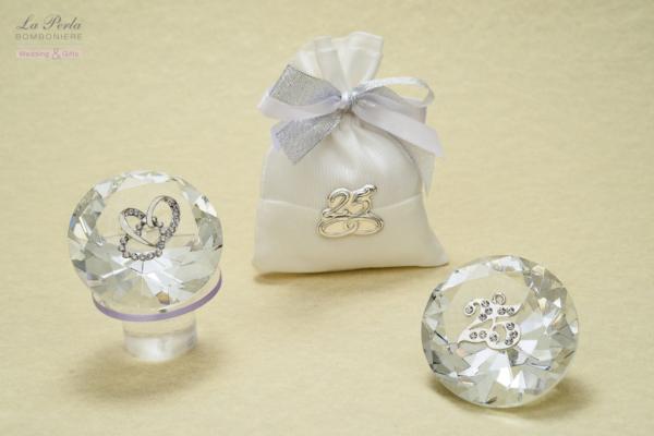 Debora Carlucci firma il prisma in cristallo con due cuori intrecciati e il 25 simbolo delle Nozze d'Argento. Sacchettino in cotone con targhetta 25° in argento bilaminato, come segnaposto.